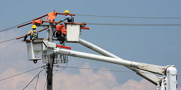Two workers in a crane repairing a power pole Hydro workers work from boom buckets to restore power to a community. 2 to 1 aspect. power line stock pictures, royalty-free photos & images
