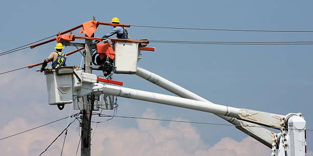 two workers in a crane repairing a power pole - elektrische leiding stockfoto's en -beelden