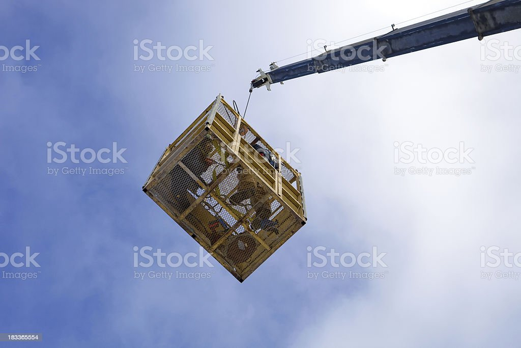 Two Workers in an Aerial Basket Suspended from a Crane stock photo
