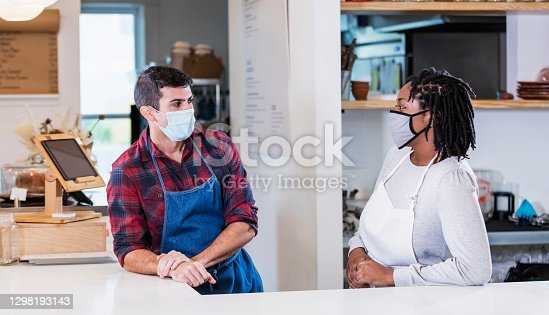 Two multi-ethnic workers standing face to face behind the checkout counter of a cafe, wearing aprons and protective face masks. They are working during the covid-19 pandemic, trying to prevent the spread of coronavirus. The man is Hispanic, in his 30s. His coworker is a young black woman in her 20s.