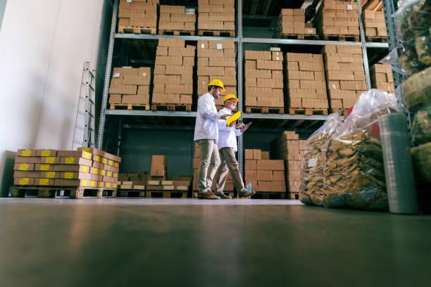twee werknemers in uniformen en helmen op de koppen lopen in de opslag en het op zoek in documenten. - netherlands map stockfoto's en -beelden