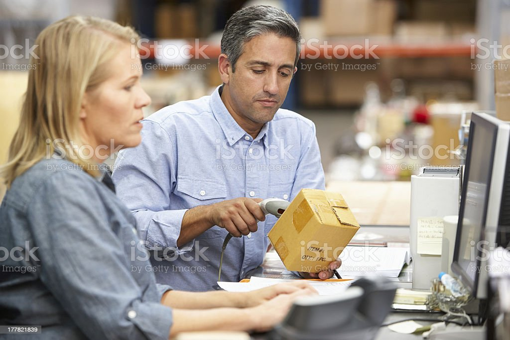 Two workers in warehouse using computer and scanning barcode stock photo