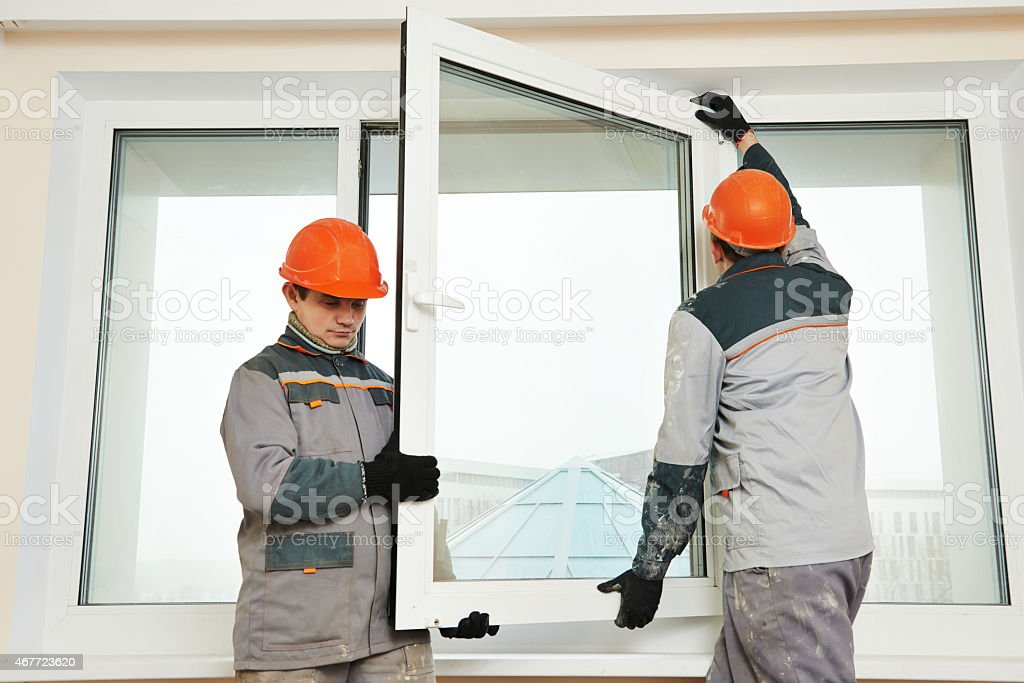 two workers installing window stock photo