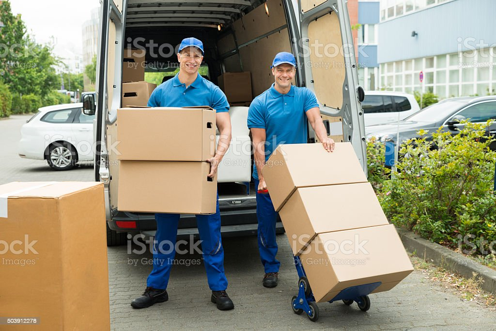 Two Workers Loading Cardboard Boxes In Truck stock photo