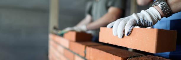 Zwei Arbeiter bauen rote Ziegelmauer auf Baustelle – Foto