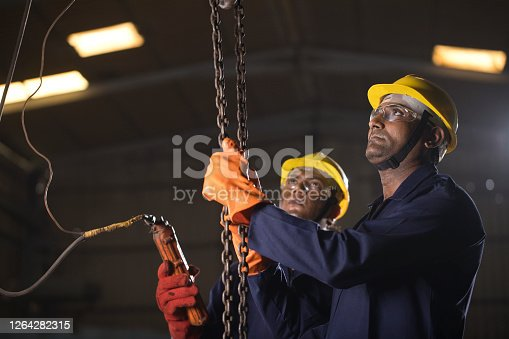 1047558948 istock photo Two workers operating chain hoist at factory 1264282315