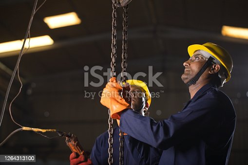 1047558948 istock photo Two workers operating chain hoist at factory 1264313100