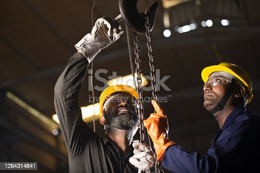 1047558948 istock photo Two workers operating chain hoist at factory 1264314841