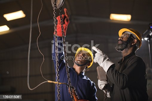 1047558948 istock photo Two workers operating chain hoist at factory 1264315081