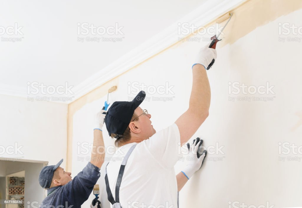 Two workers paint a wall in the room. stock photo