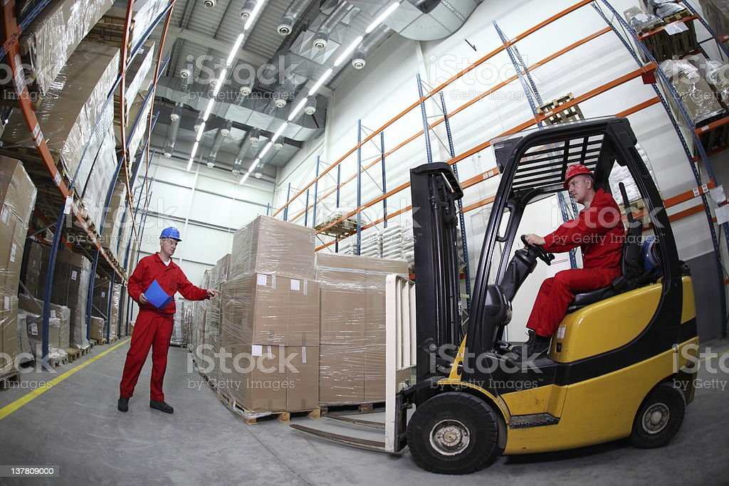 two workers reloading pallets with forklift truck stock photo