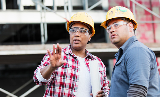 Two multi-ethnic construction workers meeting at a construction site, talking about a serious matter. They are looking up in the same direction with serious expressions. The focus is on the mature African-American woman in her 40s with her hand pointed in the direction they are looking. Her coworker is a young Hispanic man in his 20s.