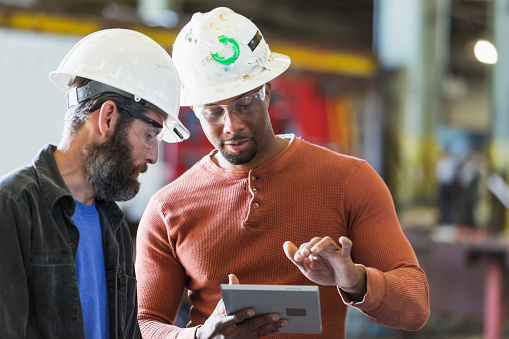 istock Two workers wearing hardhats using digital tablet 856736866