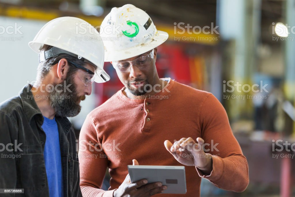 Two workers wearing hardhats using digital tablet stock photo