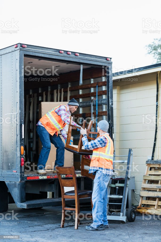 Two multi-ethnic mature workers in their 40s at the back of a truck,...