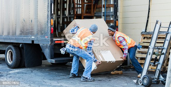 Two multi-ethnic mature workers in their 40s at the back of a truck, loading or unloading a large cardboard box. The men are wearing plaid shirts, reflective vests and jeans. They are moving merchandise for a furniture store.