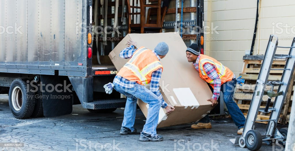 Two workers with a truck, moving large box stock photo