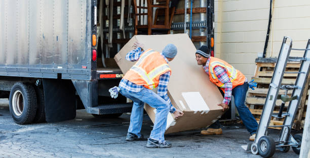 Two workers with a truck, moving large box Two multi-ethnic mature workers in their 40s at the back of a truck, loading or unloading a large cardboard box. The men are wearing plaid shirts, reflective vests and jeans. They are moving merchandise for a furniture store. retrieving stock pictures, royalty-free photos & images
