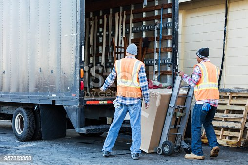 istock Two workers with a truck, moving large box 957383358
