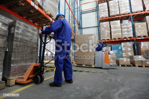 istock Two workers working in storehouse moving huge boxes 124028525