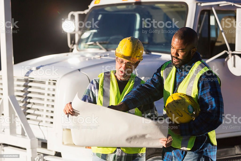 Two workmen in safety vests with truck looking at plans stock photo