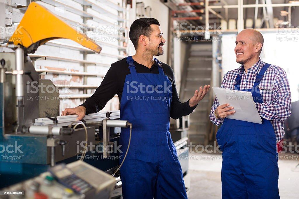 Two workmen near cutter-lathe machine stock photo