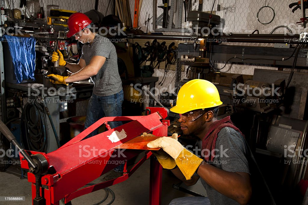 Two workmen wearing hardhats in workshop vice and metal breaker stock photo