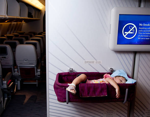 Two year old baby girl sleep in bassinet on airplane stock photo