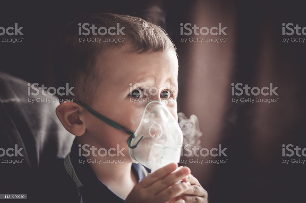 Two year old boy making inhalation with nebulizer at home. child...