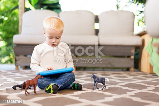 Two year old child playing on floor with tablet and toys