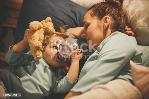 Two year old girl drinking water from the bottle in bed, holding Teddy bear and lying down next to her mother.