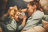 istock Two year old girl drinking water from the bottle in bed 1135725316