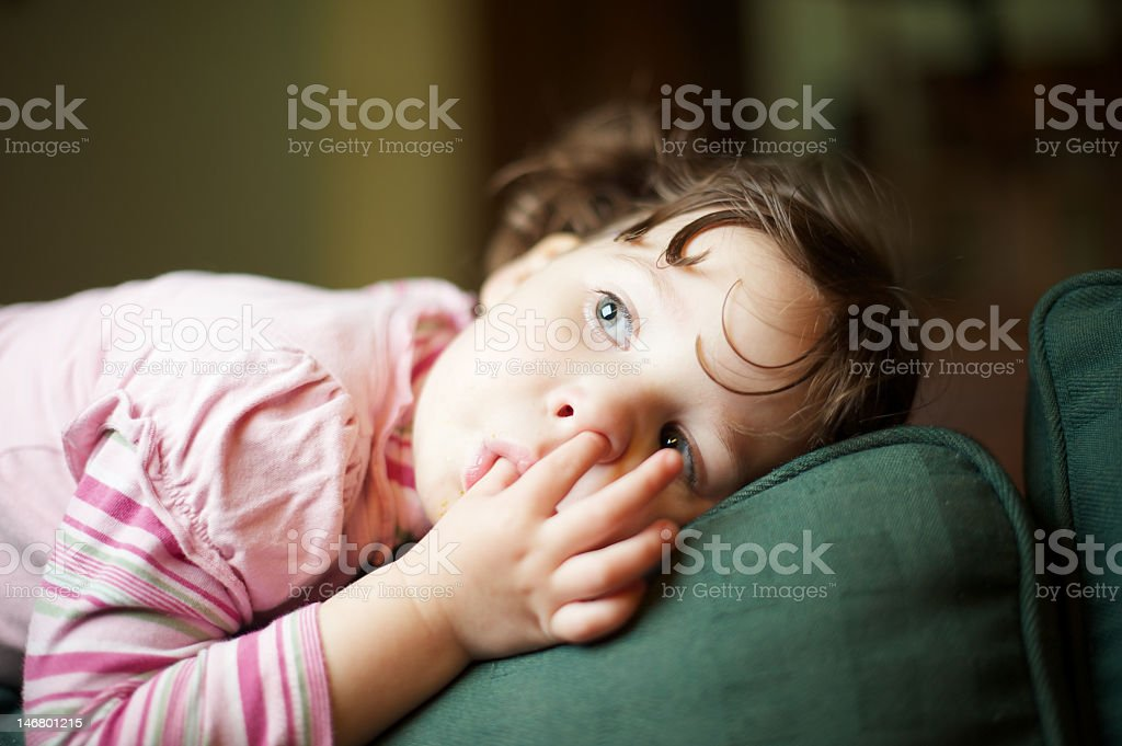 Two year old lying on the back of a sofa stock photo