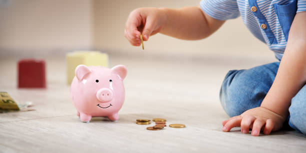 two years old child sitting on the floor and putting a coin into a piggybank two years old child sitting on the floor and putting a euro coin into a piggybank. allowance stock pictures, royalty-free photos & images