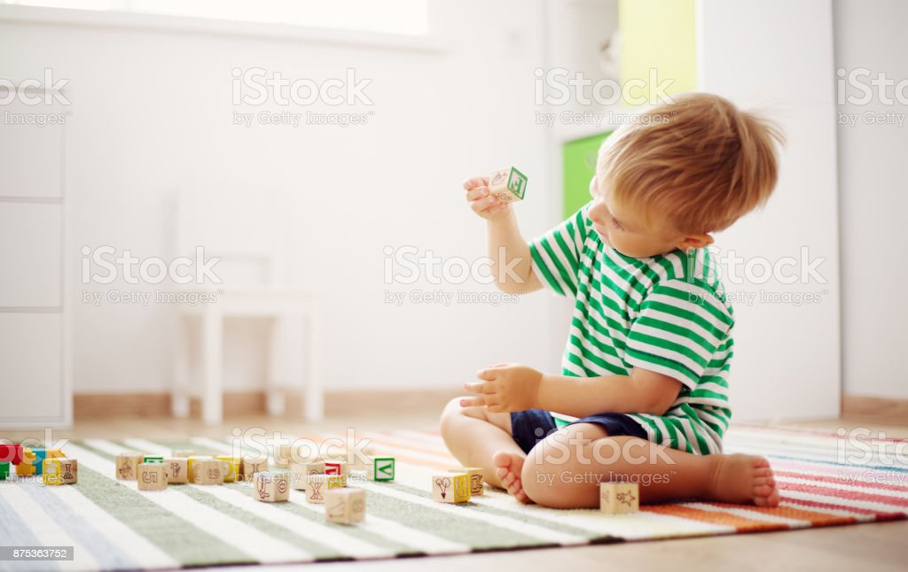 two years old child sitting on the floor with wooden cubes stock photo