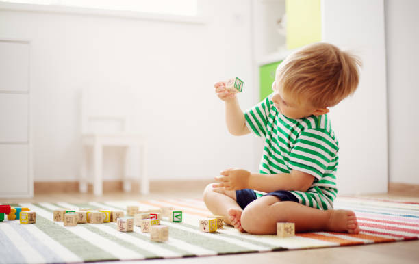 two years old child sitting on the floor with wooden cubes - foto stock