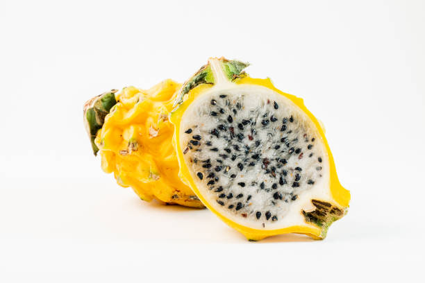Two yellow dragon fruits on a white background.  One of the fruits is sliced in half. Two yellow dragon fruits on a white background.  One of the fruits is sliced in half. pitaya stock pictures, royalty-free photos & images