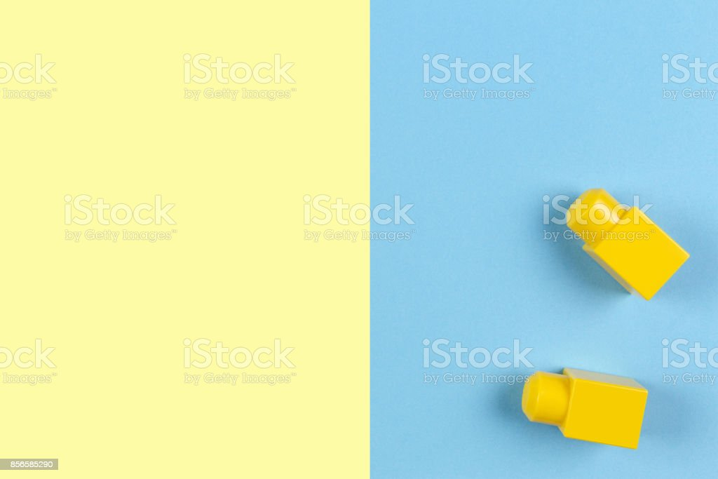 Two yellow plastic construction blocks on yellow and blue background stock photo