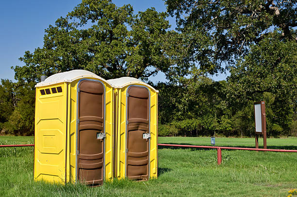 Two yellow portable toilets at a park Two yellow portable toilets at a park portable toilet stock pictures, royalty-free photos & images