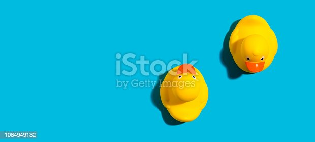 Two yellow rubber ducks on a blue background