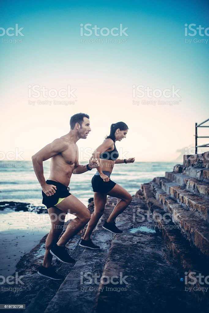 Two young adult athletes doing running exercise on staircase stock photo