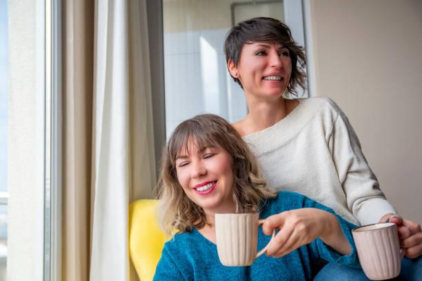 dos mujeres adultas jóvenes compartiendo momentos. - happy couple sharing a cup of coffee fotografías e imágenes de stock