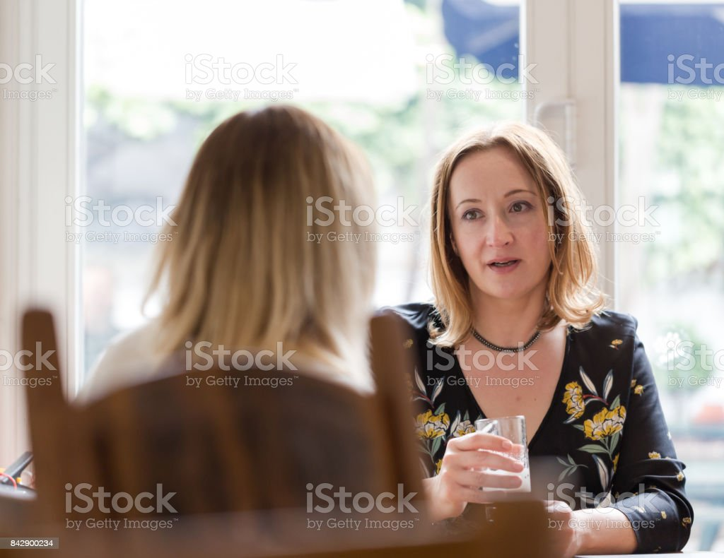 Two young adult women having friends chat in pub stock photo