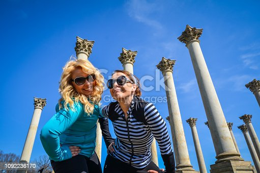 Two young adult women standing and smiling next to Capitol Columns in Washington DC National Arboretum