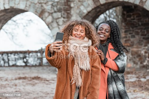 Two young adult women taking a selfie with a mobile phone outdoors in wintertime.