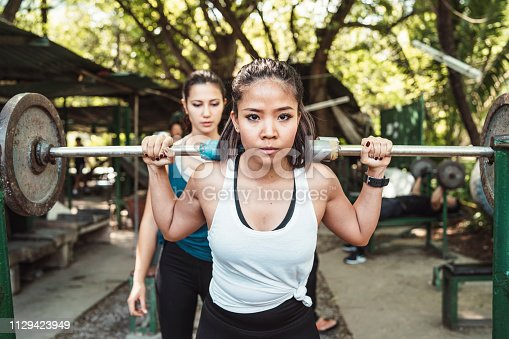 Two young adult women weight lifting outdoor with a barbell