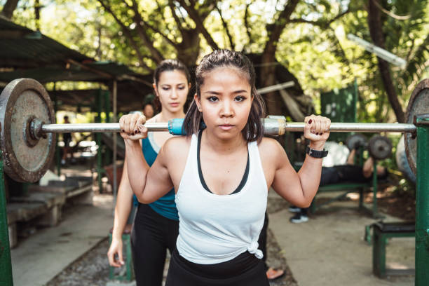 Two young adult women weight lifting outdoor stock photo