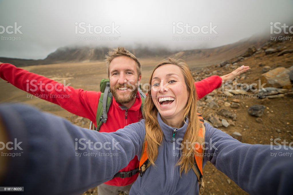 Two young adults hiking take selfie portrait stock photo
