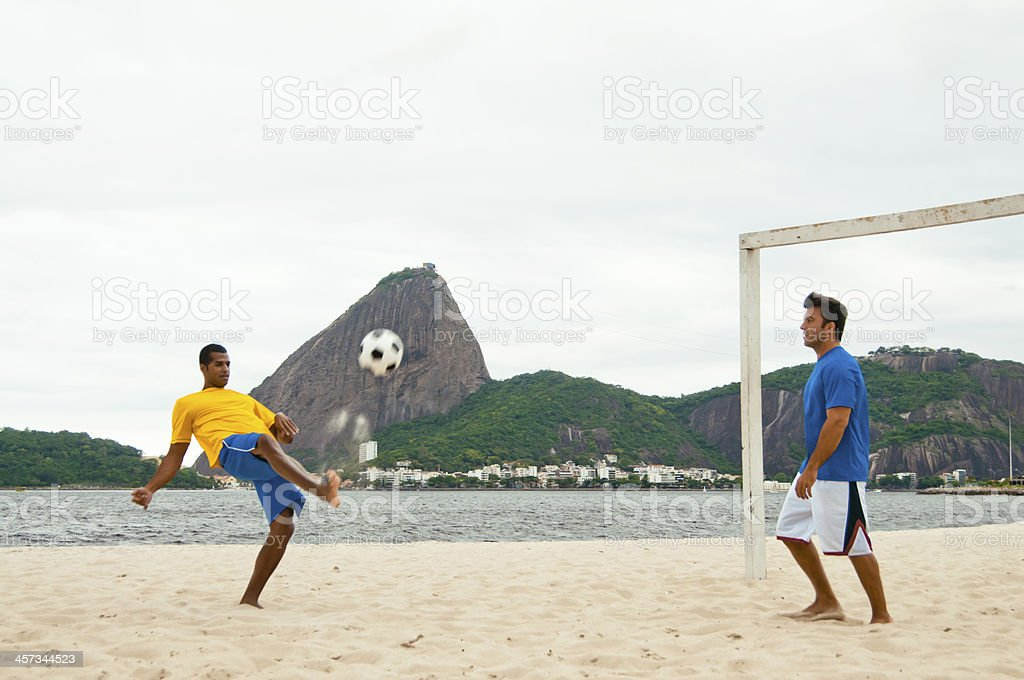 Two Young Adults Playing Football on Praia do Flamengo Beach stock photo