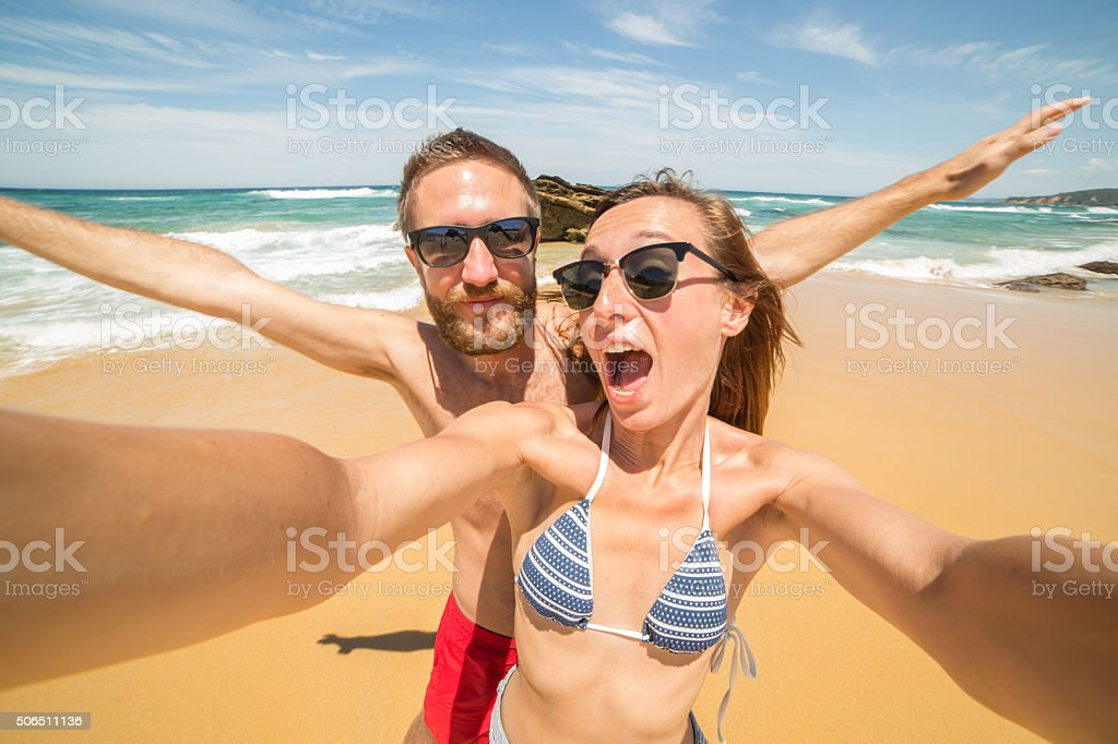 Two young adults take a selfie portrait on the beach-Summer stock photo